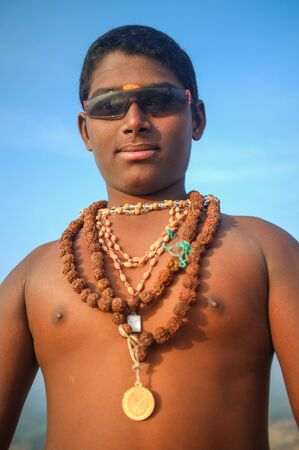 mystic: KAMALAPURAM, INDIA - 03 FEBRUARY: Young Indian pilgrim with religious necklaces and sunglasses on hilltop Editorial