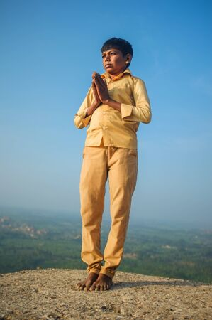 indian culture: KAMALAPURAM, INDIA - 03 FEBRUARY: Indian pilgrim with hands in praying position on hilltop