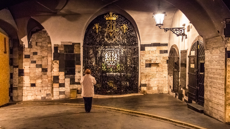 main gate: ZAGREB, CROATIA - 11 MARCH 2015: Woman praying inside Kamenita vrata, a place of prayer in the upper town. Editorial