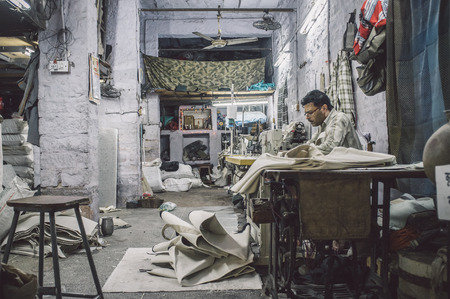 underpaid: JODHPUR, INDIA - 10 FEBRUARY 2015: Tailor at work in textile factory after working hours. Post-processed with grain and texture.