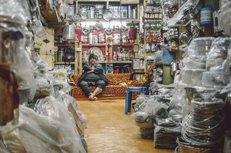 closing time: JODHPUR, INDIA - 07 FEBRUARY 2015: Shop owner with hat sitting on couch and resting before closing time. Post-processed with added grain and texture. Editorial