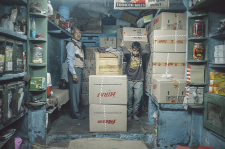 storeroom: JODHPUR, INDIA - 07 FEBRUARY 2015: Shop owner and young worker in storeroom of tobacco shop with Miraj chewing tobacco in boxes. Post-processed with added grain and texture.