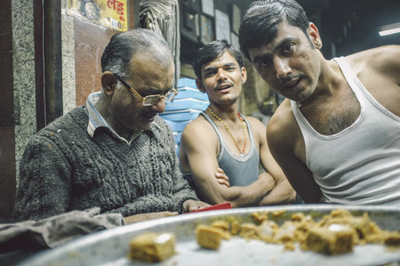 underpaid: JODHPUR, INDIA - 07 FEBRUARY 2015: Candy store owner next to two workers finishing full day shift. Workers around India are mostly underpaid and overworked. Editorial