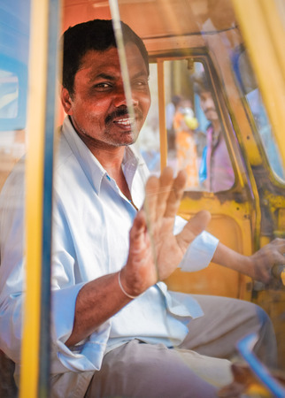 gesticulating: KAMALAPURAM, INDIA - 02 FABRUARY 2015: Indian delivery man gesticulating while passing by in a three-wheeler