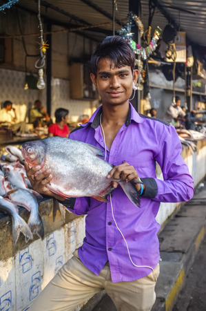 dhobi ghat: MUMBAI, INDIA - 08 JANUARY 2015: Customer on a fishmarket next to Dhobi ghat posing with a fish.