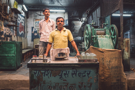 specialised: JODHPUR, INDIA - 17 FEBRUARY 2015: Vendor makes sugarcane juice in specialised machine. Finished juice is stored and covered with cotton rag. Post-processed with grain and texture.