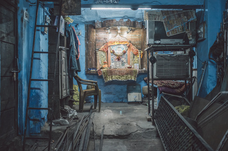 festival scales: JODHPUR, INDIA - 17 FEBRUARY 2015: Empty mechanics shop with small shiva temple in background. Post-processed with grain and texture. Editorial
