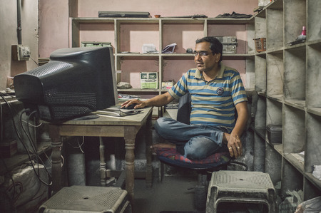 sits on a chair: JODHPUR, INDIA - 16 FEBRUARY 2015: Indian man sits in office cross-legged on chair in front of computer screen. Post-processed with grain and texture.