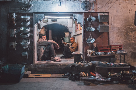 closing time: JODHPUR, INDIA - 16 FEBRUARY 2015: Two workers sit and rest before closing time. Stores with kitchen pottery made from metal are common on Asian markets. Post-processed with grain and texture. Editorial