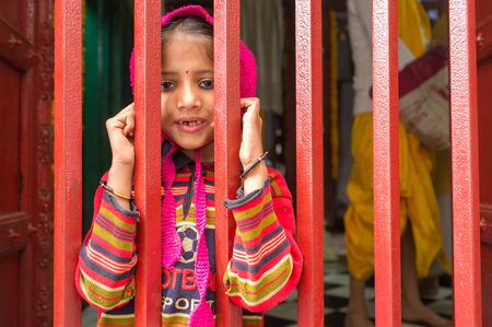 bindi: VARANASI, INDIA - 20 FEBRUARY 2015: Little girl with runny nose looks through closed fence of a small temple. Editorial