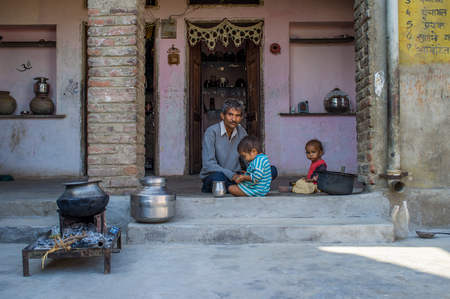 sits: GODWAR REGION, INDIA - 13 FEBRUARY 2015: Father sits after breakfast with children in doorway of courtyard. Editorial
