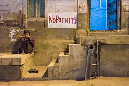 """no entrance: Jodhpur, India - 10 de febrero 2015: El hombre mayor se sienta con las piernas cruzadas cerca de la entrada a casa y """"No hay aparcamiento"""" signo. Editorial"""