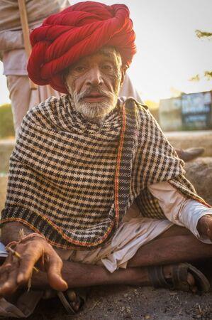 earing: GODWAR REGION, INDIA - 14 FEBRUARY 2015: Elderly Rabari tribesman with red turban and blanket around the shoulders smokes beedi. Rabari or Rewari are an Indian community in the state of Gujarat.