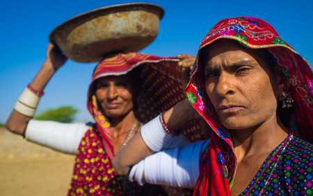 nosering: GODWAR REGION, INDIA - 14 FEBRUARY 2015: Rabari tribeswomen stand in field wearing sarees and upper-arm bracelets. One balances bucket on head. Rabari are an Indian community in the state of Gujarat.