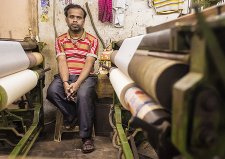 textile machine: VARANASI, INDIA - 21 FEBRUARY 2015: Worker sits on chair next to textile machine in small factory.