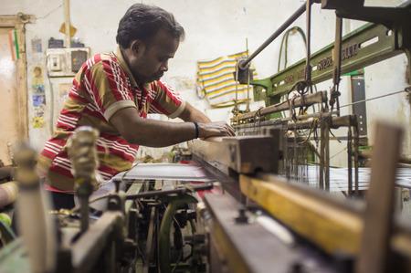 textile machine: VARANASI, INDIA - 21 FEBRUARY 2015: Worker repairs textile machine in small factory.
