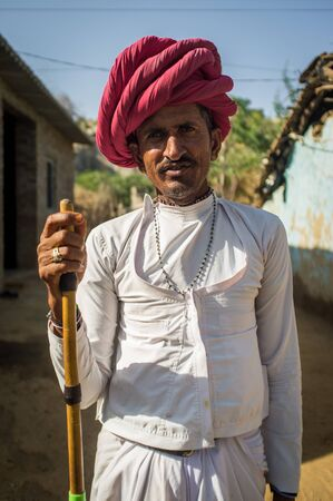 herding: GODWAR REGION, INDIA - 13 FEBRUARY 2015: Rabari tribesman stands in courtyard of home wearing traditional clothes and holds herding stick. Post-processed with grain, texture and colour effect. Editorial