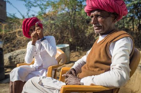neighbour: GODWAR REGION, INDIA - 13 FEBRUARY 2015: Elderly Rabari tribesman sits with neighbour who smokes chillum. Rabari or Rewari are an Indian community in the state of Gujarat.