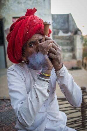 gujarat: GODWAR REGION, INDIA - 12 FEBRUARY 2015: Rabari tribesman smokes chillum. Rabari or Rewari are an Indian community in the state of Gujarat. Editorial