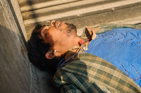passed out: JODHPUR, INDIA - 10 FEBRUARY 2015: Drunk Indian man passed out on street.