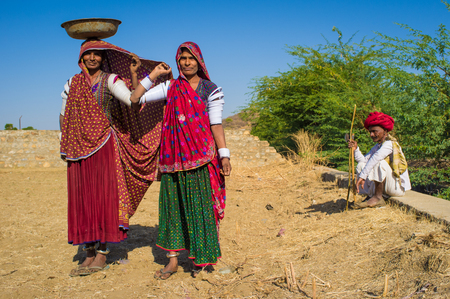 nosering: GODWAR REGION, INDIA - 14 FEBRUARY 2015: Rabari women stand in field wearing sarees and upper-arm bracelets with man sitting in background. Rabari are an Indian community in the state of Gujarat. Editorial