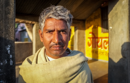 sholders: GODWAR REGION, INDIA - 14 FEBRUARY 2015: Adult Indian man with grey hair stands in street. Editorial
