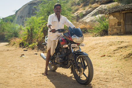 showoff: GODWAR REGION, INDIA - 13 FEBRUARY 2015: Indian man shows off his motorbike in courtyard.