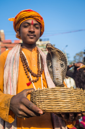 bindi: VARANASI, INDIA - 23 FEBRUARY 2015: Indian boy dressed up in religious clothes holds cobra in basket. Editorial