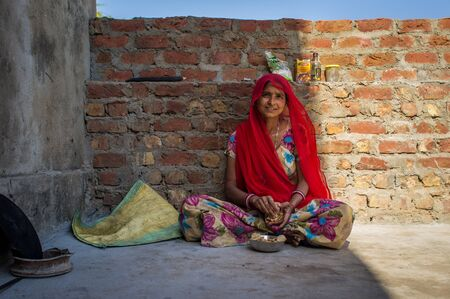eats: GODWAR REGION, INDIA - 13 FEBRUARY 2015: Indian woman in sari sits and eats chapati for breakfast.