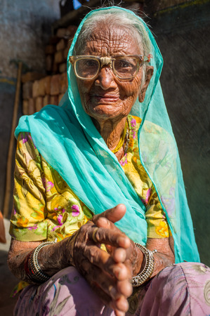 repaired: GODWAR REGION, INDIA - 13 FEBRUARY 2015: Elderly Indian woman in sari with covered head and repaired glasses sits in doorway of home. Editorial