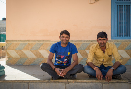 crosslegged: GODWAR REGION, INDIA - 15 FEBRUARY 2015: Two typical modern Indian men sit cross-legged on ground in front of home. Editorial