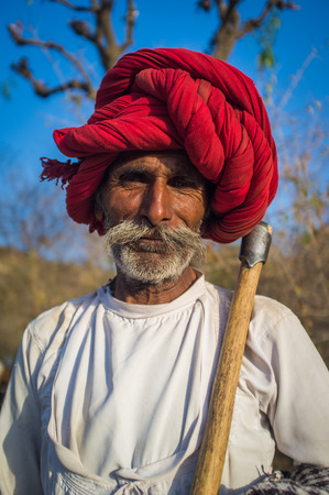 gujarat: GODWAR REGION, INDIA - 13 FEBRUARY 2015: Rabari tribesman holds traditional axe and stands on field. Rabari or Rewari are an Indian community in the state of Gujarat.