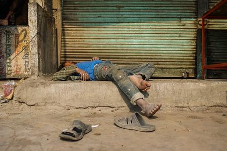 alcoholic man: JODHPUR, INDIA - 10 FEBRUARY 2015: Drunk Indian man passed out on street.