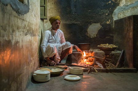 ring of fire: GODWAR REGION, INDIA - 12 FEBRUARY 2015: Indian man dressed in traditional clothes makes chapati on open fire in old kitchen. Post-processed with grain, texture and colour effect.
