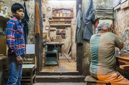 labourers: JODHPUR, INDIA - 10 FEBRUARY 2015: Young  apprentice awaits instructions while carpenter works. Children are used as cheap labourers through out Asia. Editorial