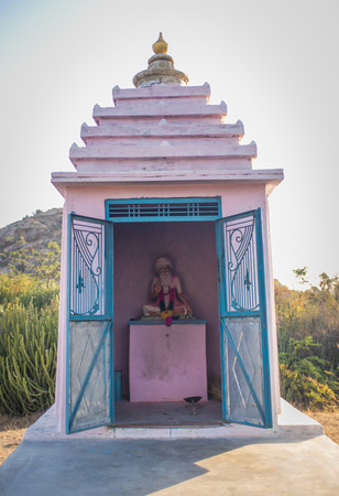 dedicated: Small temple dedicated to local holy man. Statue of man sitting cross-legged and waving decorated with flowers.