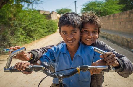 hait: GODWAR REGION, INDIA - 15 FEBRUARY 2015: Two boys on a bicycle in empty village street.
