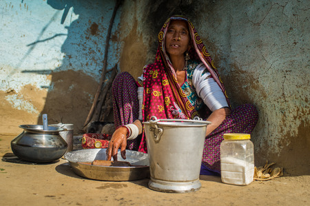 gujarat: GODWAR REGION, INDIA - 13 FEBRUARY 2015: Rabari tribeswoman in sari decorated with traditional upper-arm bracelets cleans dishes. Rabari or Rewari are an Indian community from Gujarat.