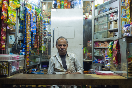 stimulant: JODHPUR, INDIA - 11 FEBRUARY 2015: Indian vendor sits in shop with gutka hanging in background with other products. Gutka has mild stimulant effect. Post-processed with grain and texture.