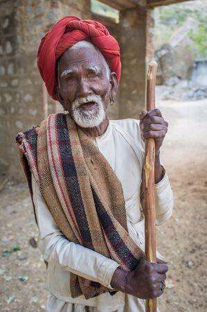 gujarat: GODWAR REGION, INDIA - 13 FEBRUARY 2015: Blind Rabari tribesman holds stick in courtyard. Rabari or Rewari are an Indian community in the state of Gujarat.