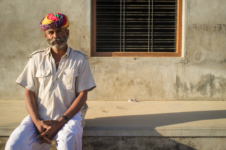 14 february: GODWAR REGION, INDIA - 14 FEBRUARY 2015: Adult Indian man with colorful turban and curled mustache sits in street. Editorial