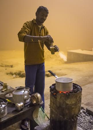 street vendor: VARANASI, INDIA - 20 FEBRUARY 2015: Street vendor prepares milky tea, called chai, on coal oven in Varanasi ghat.