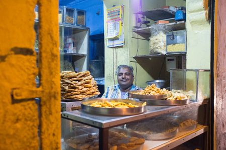 plates of food: JODHPUR, INDIA - 16 FEBRUARY 2015: Vendor sits in store with food on metal plates.