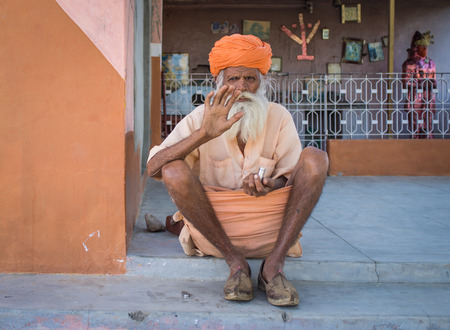 sitting on the ground: GODWAR, INDIA - 12 FEBRUARY 2015: Elderly Indian tribesman with turban in lungi sits on ground in front of temple and waves.