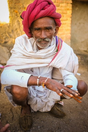 bracelet tattoo: GODWAR REGION, INDIA - 14 FEBRUARY 2015: Elderly Rabari tribesman with red turban and blanket around the shoulders. Post-processed with grain, texture and colour effect.
