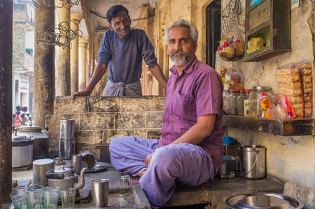 VARANASI, INDIA - 21 FEBRUARY 2015: Street vendor selling milky tea sits in shop while neighbouring carpenter stands next to him. Post-processed with grain, texture and colour effect.