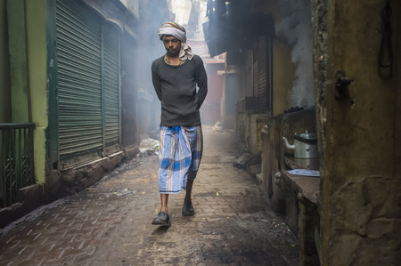 milk mustache: VARANASI, INDIA - 20 FEBRUARY 2015: Man walking through street filled with smoke. Coal ovens are used as source of heat for making milky tea.