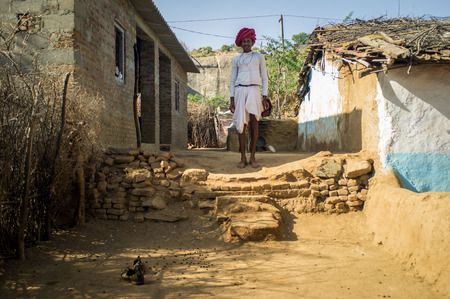 gujarat: GODWAR REGION, INDIA - 13 FEBRUARY 2015: Rabari tribesman stands in courtyard of home wearing traditional clothes. Rabari or Rewari are an Indian community in the state of Gujarat. Editorial