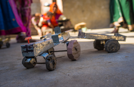 Makeshift toy tractor and trailer on ground made from metal and other materials. Father mechanic proves to be clever.