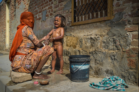 GODWAR REGION, INDIA - 15 FEBRUARY 2015: Indian mother sits and washes naked baby boy outdoors in front of home. Woman has covered face with headscarf